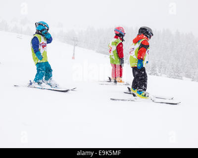 group of young children  wearing helmets and goggles learning to ski in a group lesson with  falling snow - Stock Photo