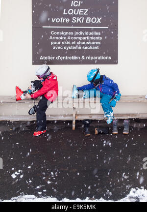 small boy and girl in ski clothing helmets and goggles sitting on a bench putting on ski boots with falling snow - Stock Photo