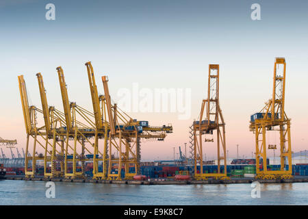 Yellow cranes move shipping containers at Barcelona's main port - Port de Barcelona - at sunrise. - Stock Photo