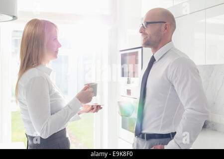 Side view of mid adult business couple talking at home - Stock Photo