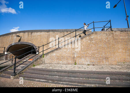 Side view of young woman walking down stairs against blue sky - Stock Photo