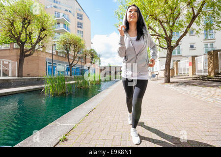 Full length of fit young woman running by canal against buildings - Stock Photo
