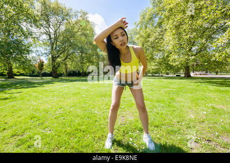Full length of tired young woman looking away while exercising in park - Stock Photo