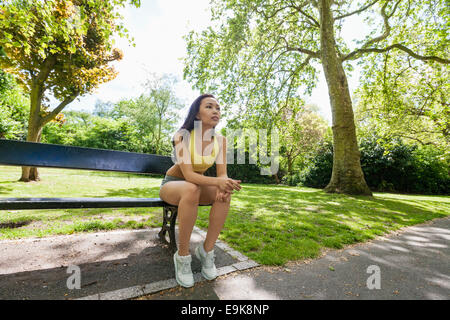 Full length of tired fit woman sitting on beach while exercising in park - Stock Photo