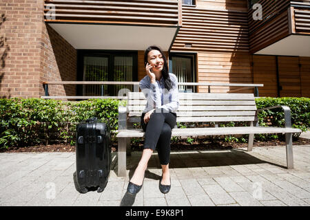 Full length of businesswoman answering cell phone while sitting by luggage on bench against building - Stock Photo