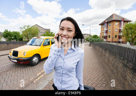 Portrait of smiling businesswoman answering cell phone on sidewalk with taxi in background - Stock Photo