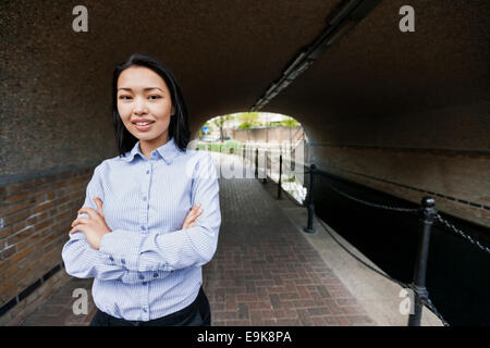 Portrait of confident businesswoman standing arms crossed by canal - Stock Photo