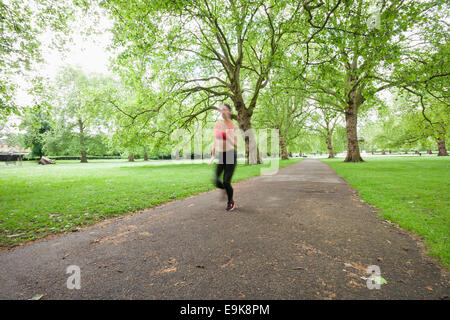 Blurred motion of woman jogging in park - Stock Photo