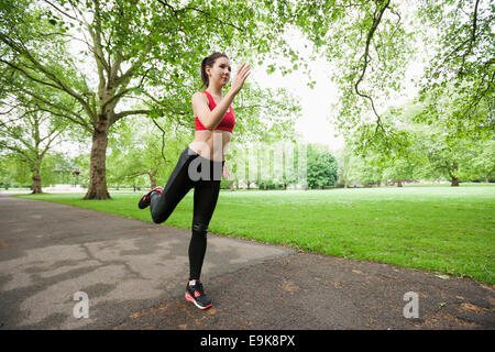 Full length of beautiful fit woman jogging in park - Stock Photo