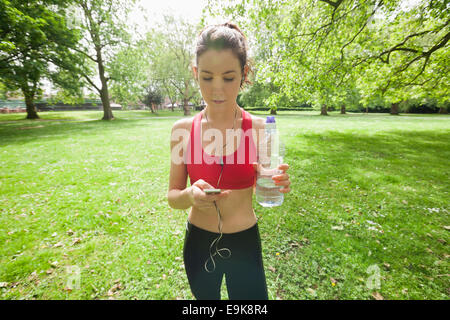 Beautiful fit woman listening to music through cell phone in park - Stock Photo