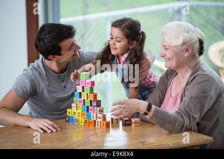 Girl playing with alphabet blocks by father and grandmother at table in house - Stock Photo