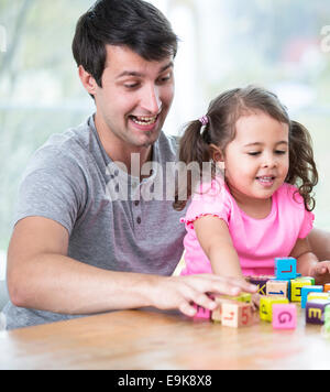 Happy father and daughter playing with building blocks at table in house - Stock Photo