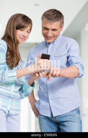 Father and daughter using smart phone at home - Stock Photo