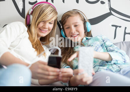 Sisters listening music through headphones at home - Stock Photo