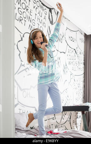 Full-length of girl listening music while singing into hairbrush on bed - Stock Photo
