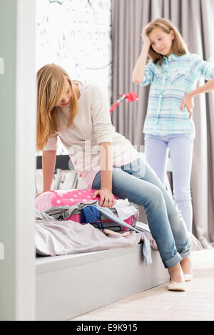 Sisters trying to close suitcase at home - Stock Photo