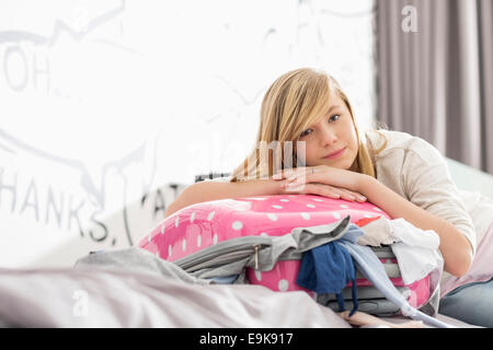 Portrait of girl relaxing on bulging suitcase at home - Stock Photo