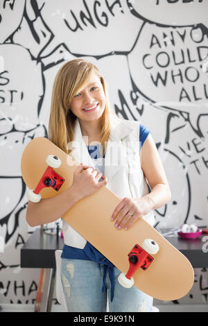 Portrait of happy teenage girl holding skateboard at home - Stock Photo