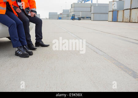 Low section of workers leaning on car in shipping yard - Stock Photo