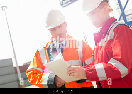 Workers discussing over tablet computer in shipping yard - Stock Photo