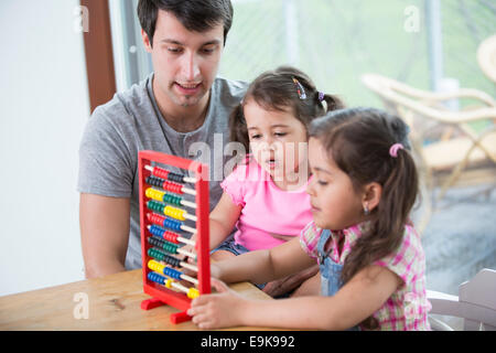 Father and daughters playing with abacus in house - Stock Photo