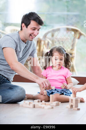 Portrait of happy father and daughters playing with abacus in house - Stock Photo