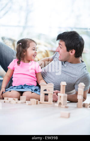 Cute girl teasing father while playing with wooden building blocks at home - Stock Photo