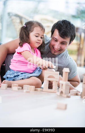 Little girl and father playing with wooden building blocks on floor - Stock Photo
