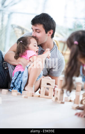 Loving father kissing daughter building blocks on floor - Stock Photo