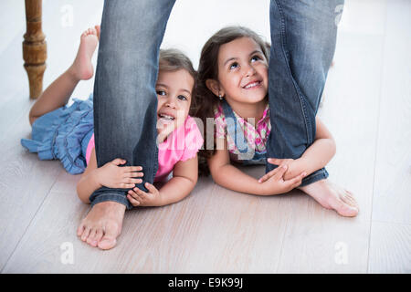 Playful girls holding father's legs on hardwood floor - Stock Photo