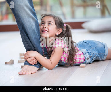 Low section of father dragging girl on hardwood floor - Stock Photo