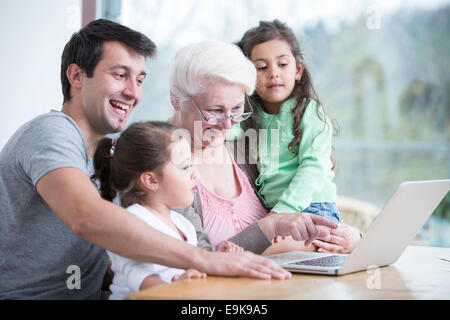 Happy three generation family using laptop at table in house - Stock Photo
