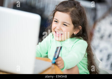 Happy girl using laptop and credit card to shop online at home - Stock Photo