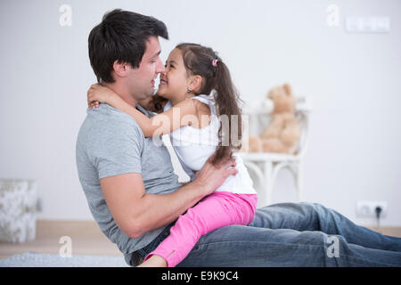 Side view of father and daughter spending quality time at home - Stock Photo