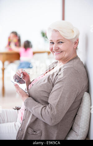 Portrait of happy senior woman using digital tablet with stylus at home - Stock Photo