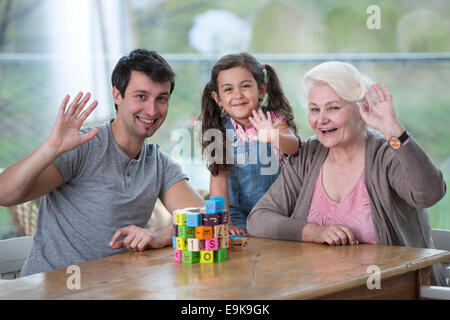 Portrait of senior woman with son and granddaughter waving hands at table - Stock Photo