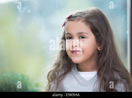 Portrait of cute little girl against glass window at home - Stock Photo