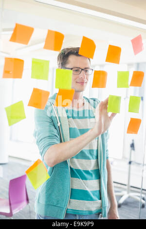 Smiling businessman reading sticky notes on glass wall in creative office - Stock Photo
