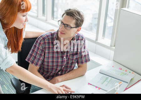 Business couple looking at each other while using laptop in creative office - Stock Photo