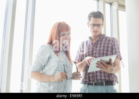 Creative businesspeople using digital tablet together in office - Stock Photo