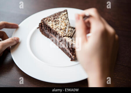 Close-up of woman's hand holding fork to chocolate pastry - Stock Photo