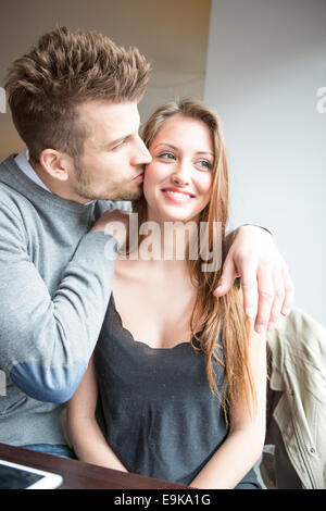 Romantic young man kissing woman in cafe - Stock Photo