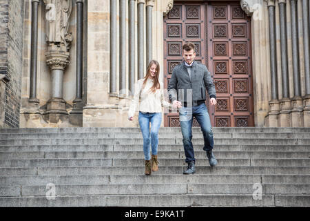 Full length of young couple moving down steps against building - Stock Photo