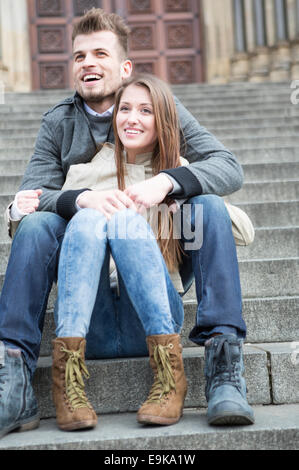Full length of young couple sitting on steps outdoors - Stock Photo