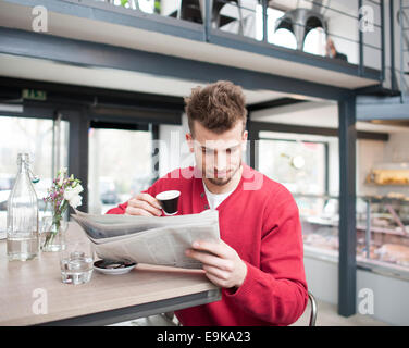 Young man reading newspaper while drinking coffee in cafe - Stock Photo