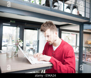 Young man using laptop in cafe - Stock Photo