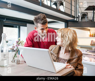Young couple looking at each other while using laptop in cafe - Stock Photo