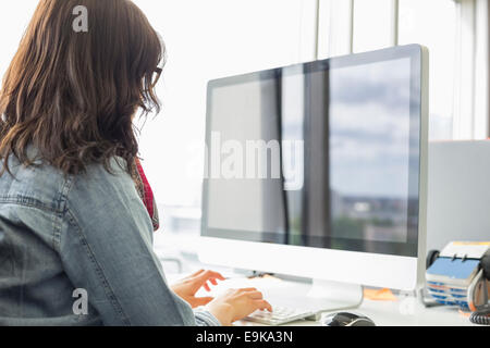 Rear view of businesswoman using desktop computer in creative office - Stock Photo