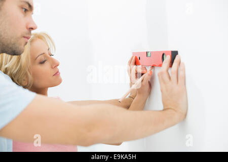 Couple marking on wall with level in new house - Stock Photo