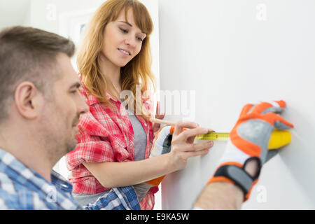 Couple using tape measure on wall - Stock Photo